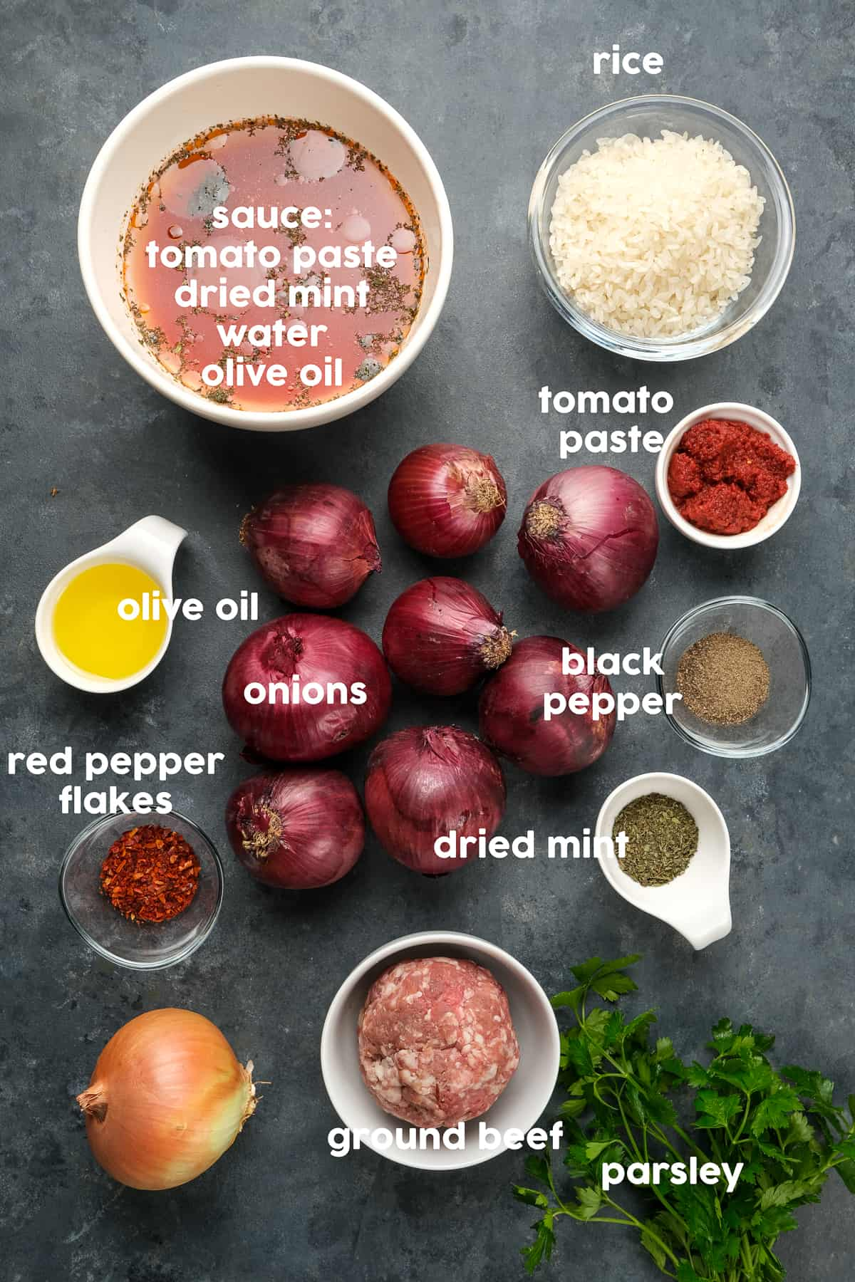 Purple onions, tomato paste, ground beef, rice, red pepper flakes, dried mint, tomato sauce, black pepper, dried mint, parsley on a dark background.