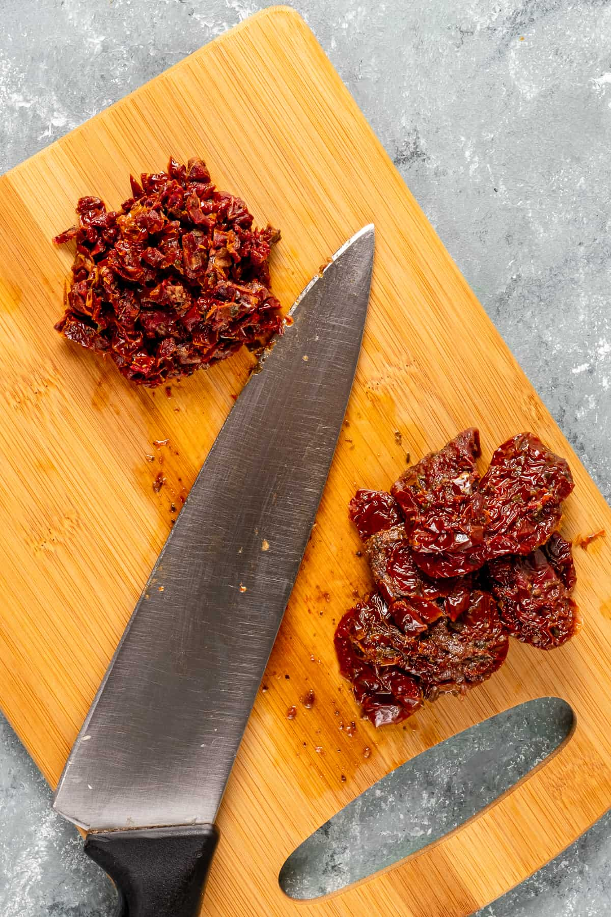 Sun-dried tomatoes whole and finely chopped on a wooden board and a knife in between them.