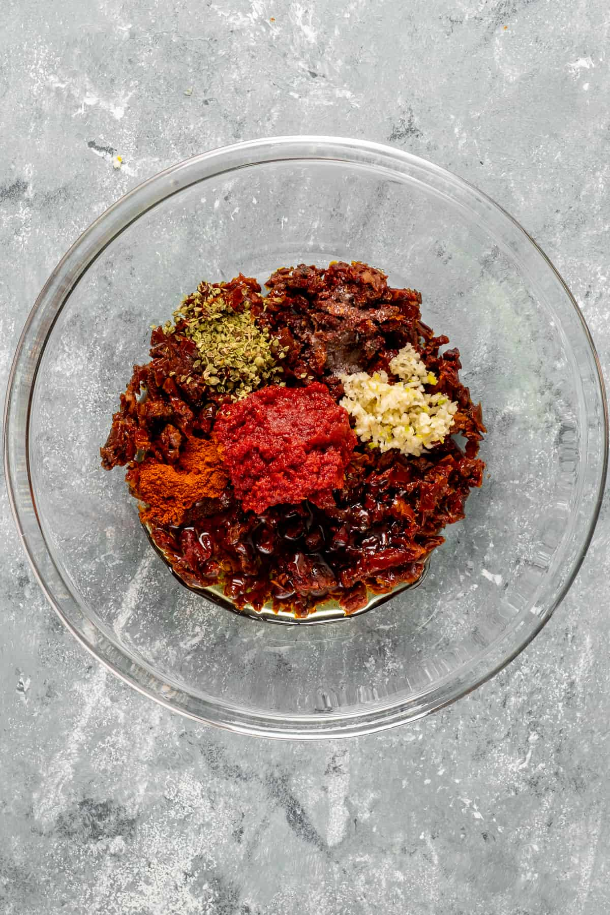 Spices, chopped sun-dried tomatoes, minced garlic and tomato paste in a glass mixing bowl.