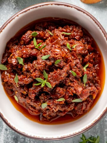 Spicy sun-dried tomato dip in a white bowl