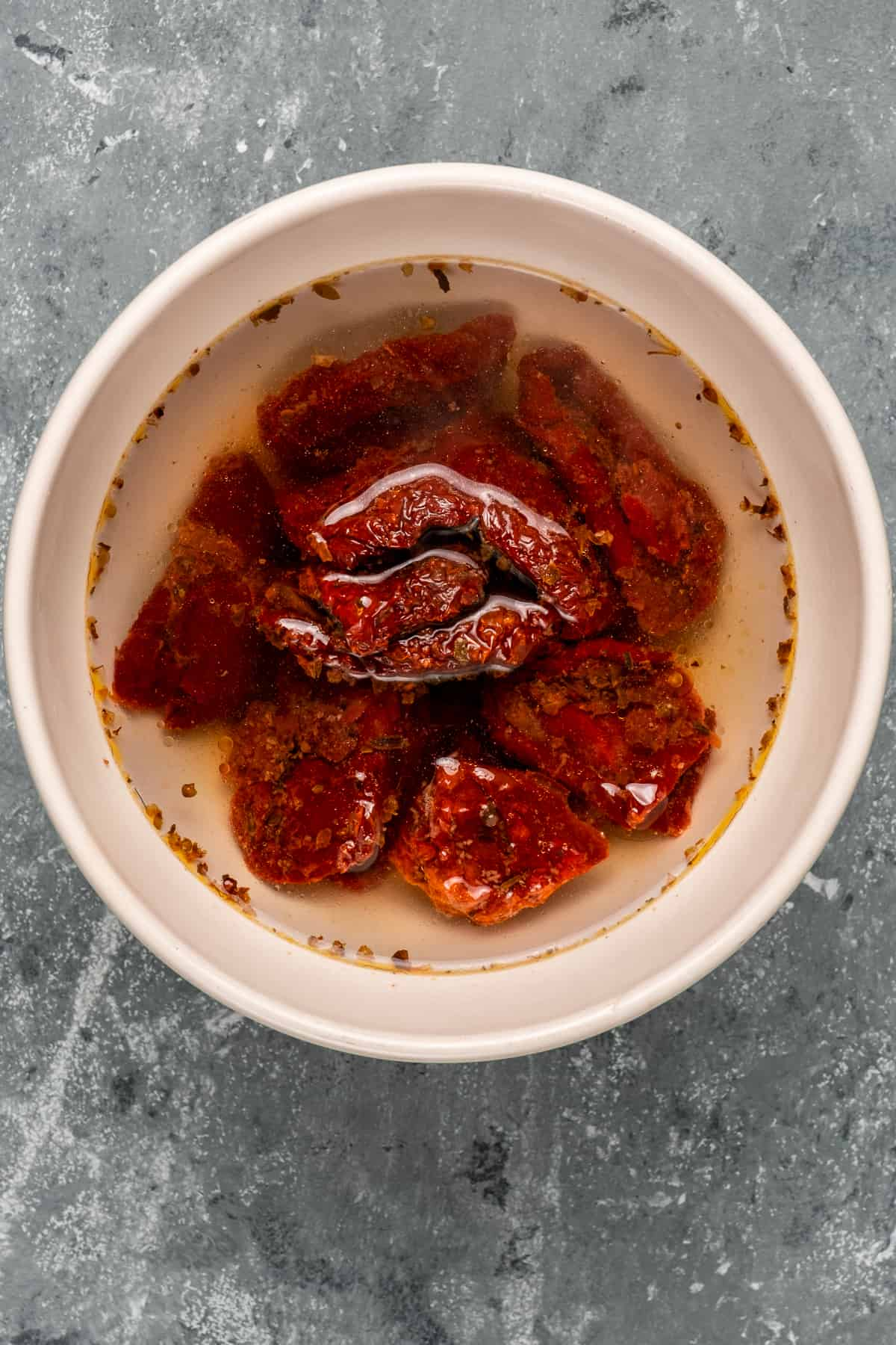 Sun-dried tomatoes soaked in water in a white bowl on a grey background.