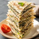 Spinach and cheese filled gozleme served in a stack on a white plate and a half of a cherry tomato on the side.