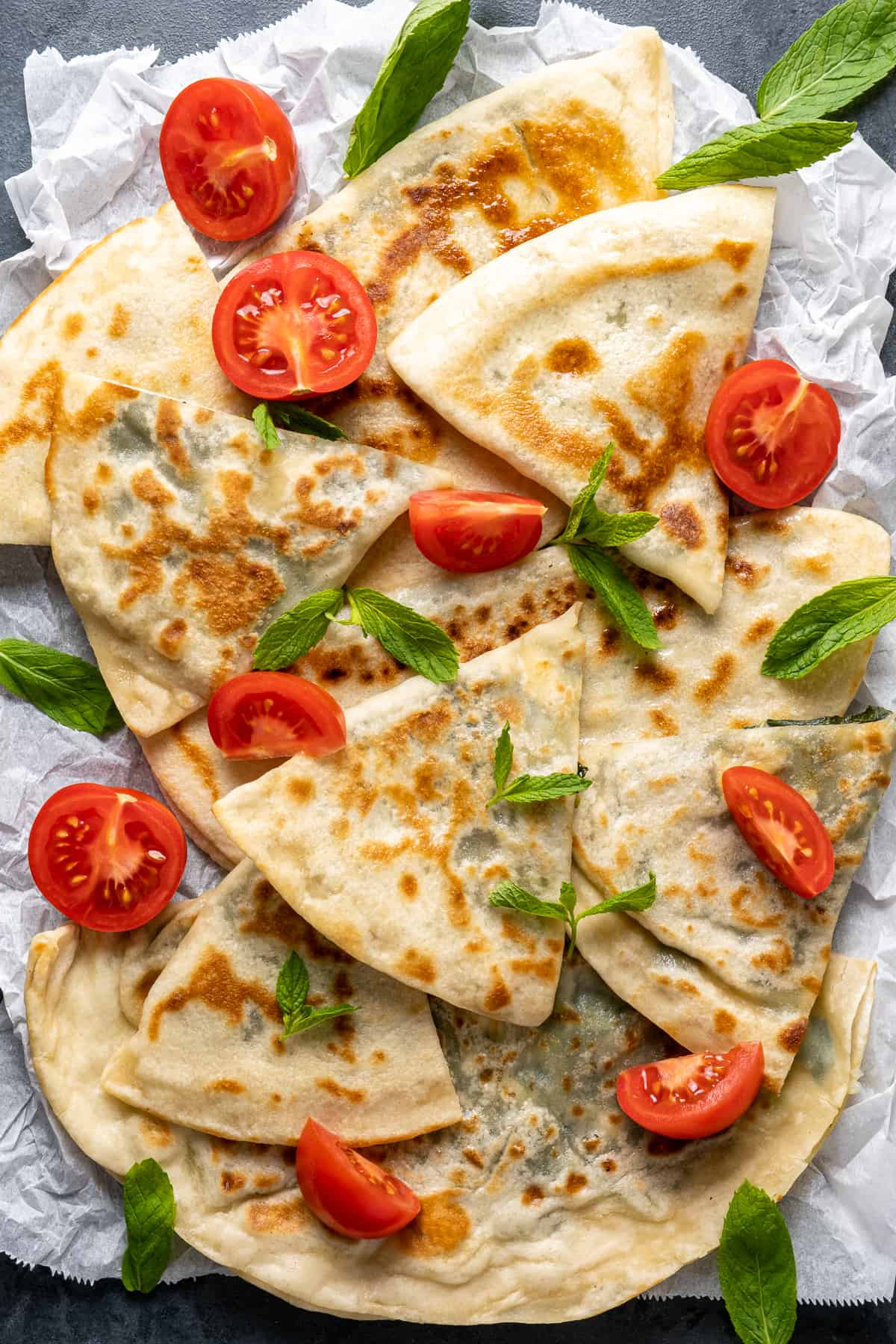 Gözleme sliced in triangles served with halved cherry tomatoes and fresh mint leaves.