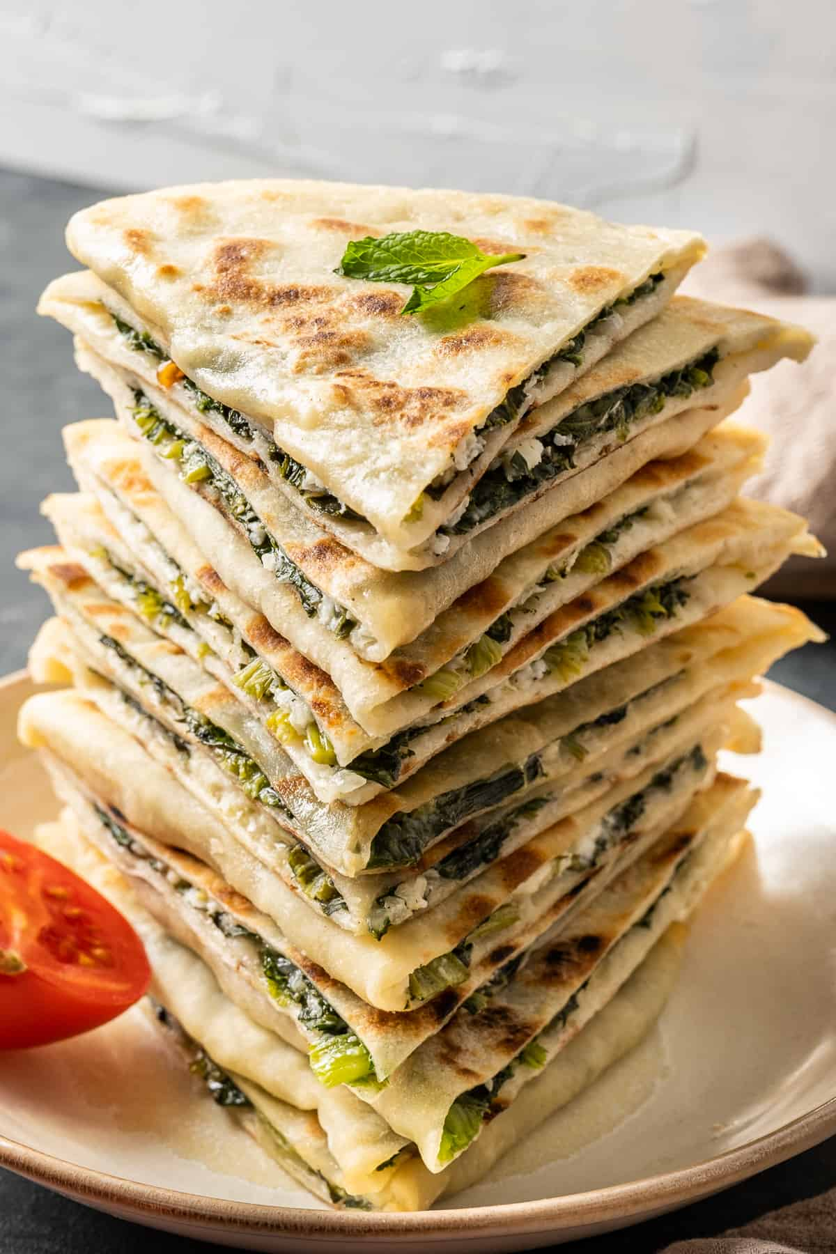 A stack of gozleme filled with spinach and cheese and a sprig of fresh mint on the top.