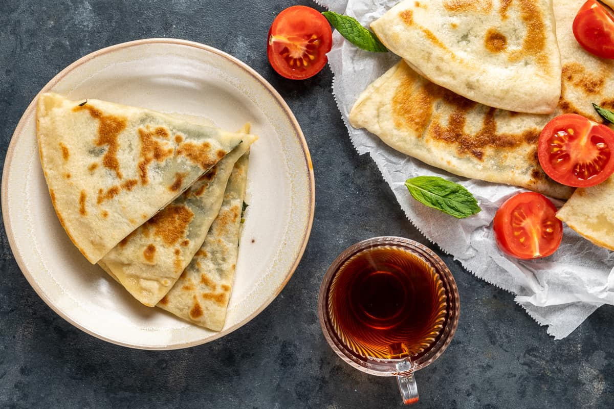 Gozleme slices on a plate and more on a larger plate accompanied by a glass cup of Turkish tea.