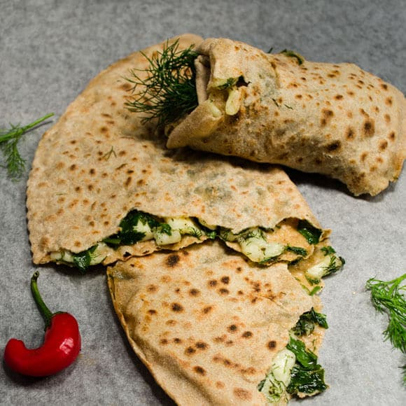 Homemade Turkish Gozleme with cheese and herbs on a grey background.