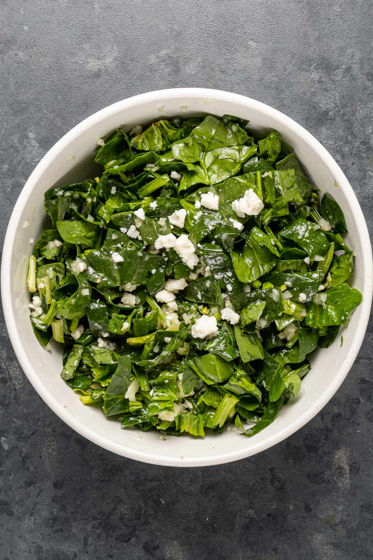 Spinach and cheese filling mixture in a white bowl
