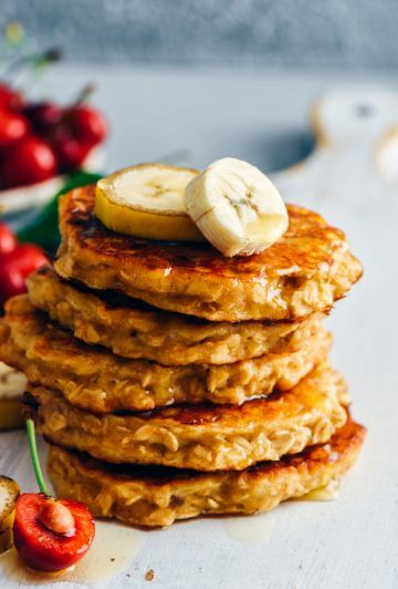 A stack of healthy banana pancakes with oatmeal topped with banana slices on a white board. Cherries and banana slices accompany.