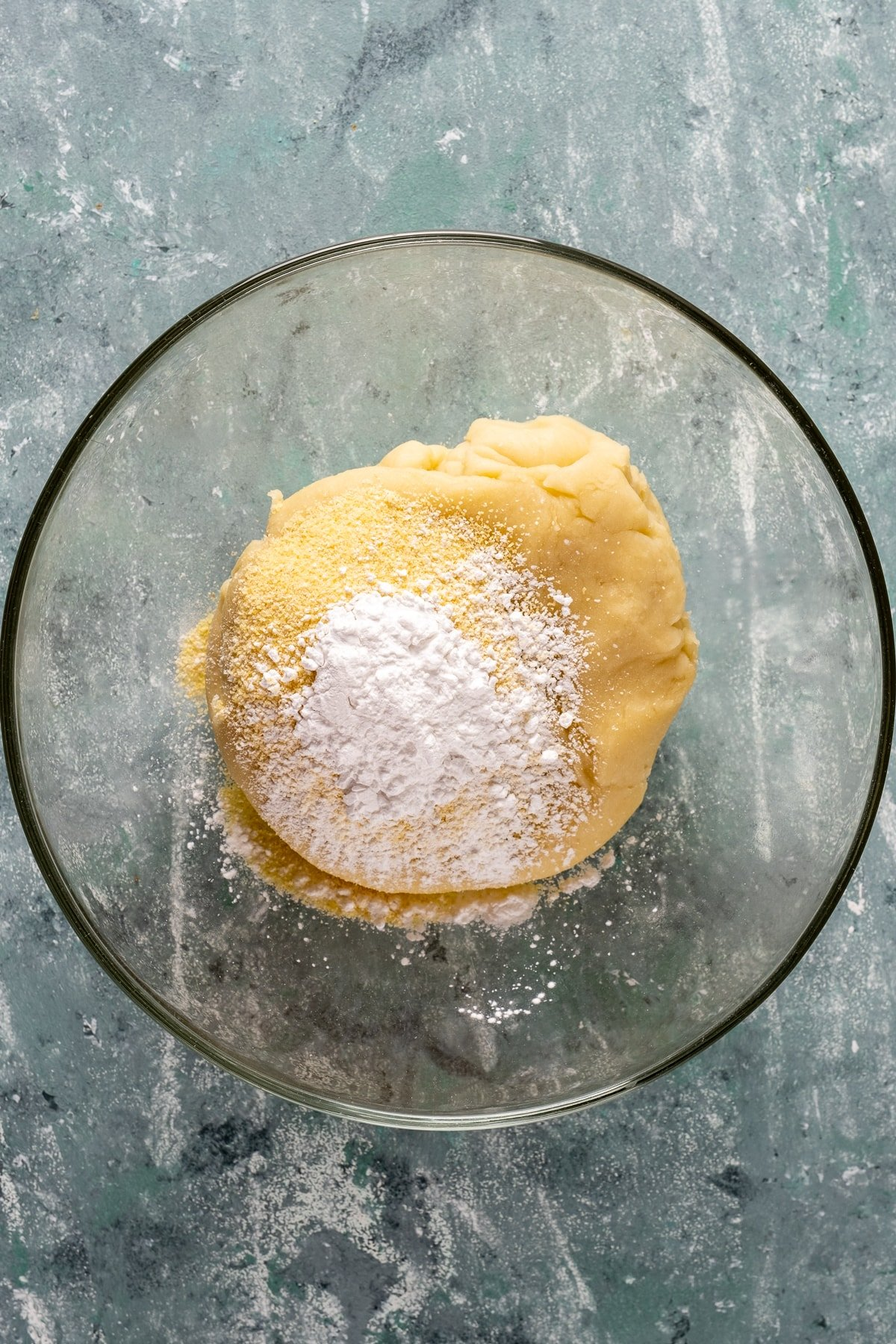 Tulumba dessert dough topped with cornstarch in a glass mixing bowl.