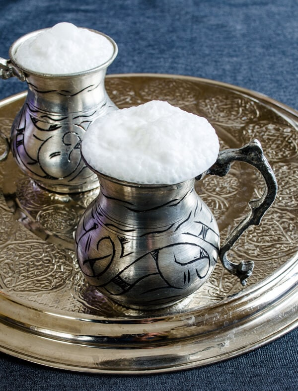 Turkish yogurt drink ayran photographed in two traditional copper cups on a copper plate.