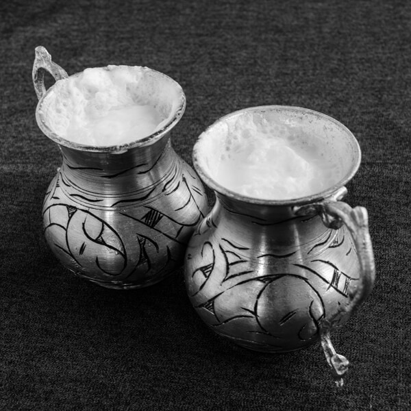 Turkish yogurt drink ayran photographed in two traditional copper cups.