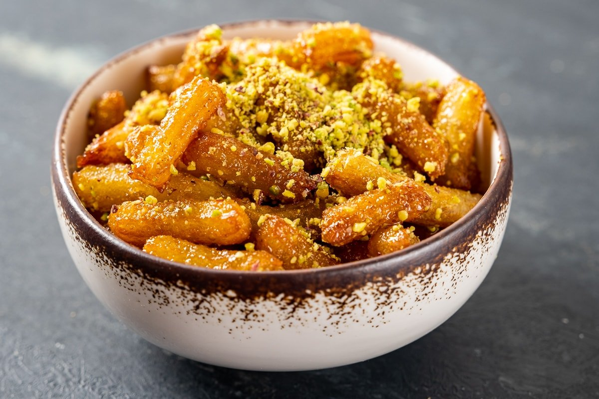 Syrupy tulumba dessert topped with ground pistachio photographed in a bowl.