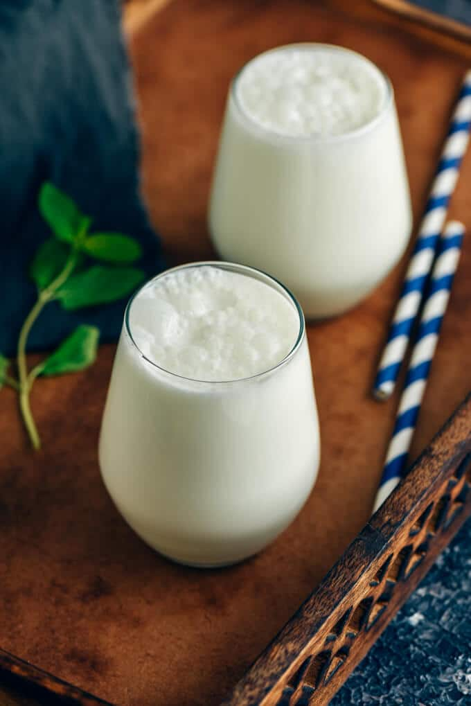 Two glasses of Turkish yogurt drink ayran photographed in a wooden tray.