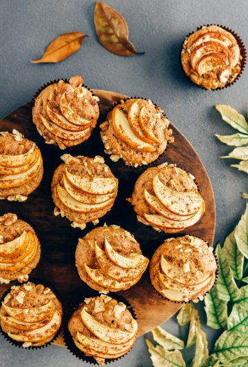 Healthy apple muffins served on a wooden stand on a dark grey backdrop accompanied by fall leaves.