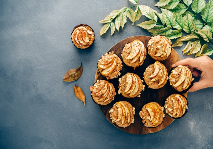 Apple cinnamon muffins served on a wooden stand on a dark grey backdrop accompanied by fall leaves.