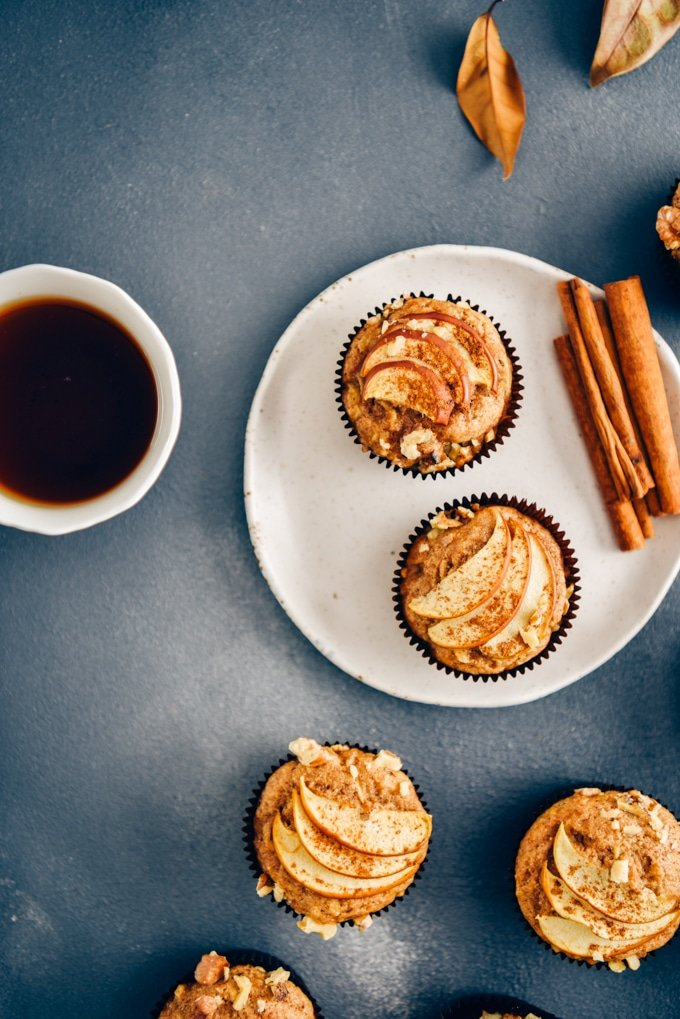 Easy apple muffins on a dark grey backdrop accompanied by fall leaves, a cup of tea, a plate and cinnamon sticks.