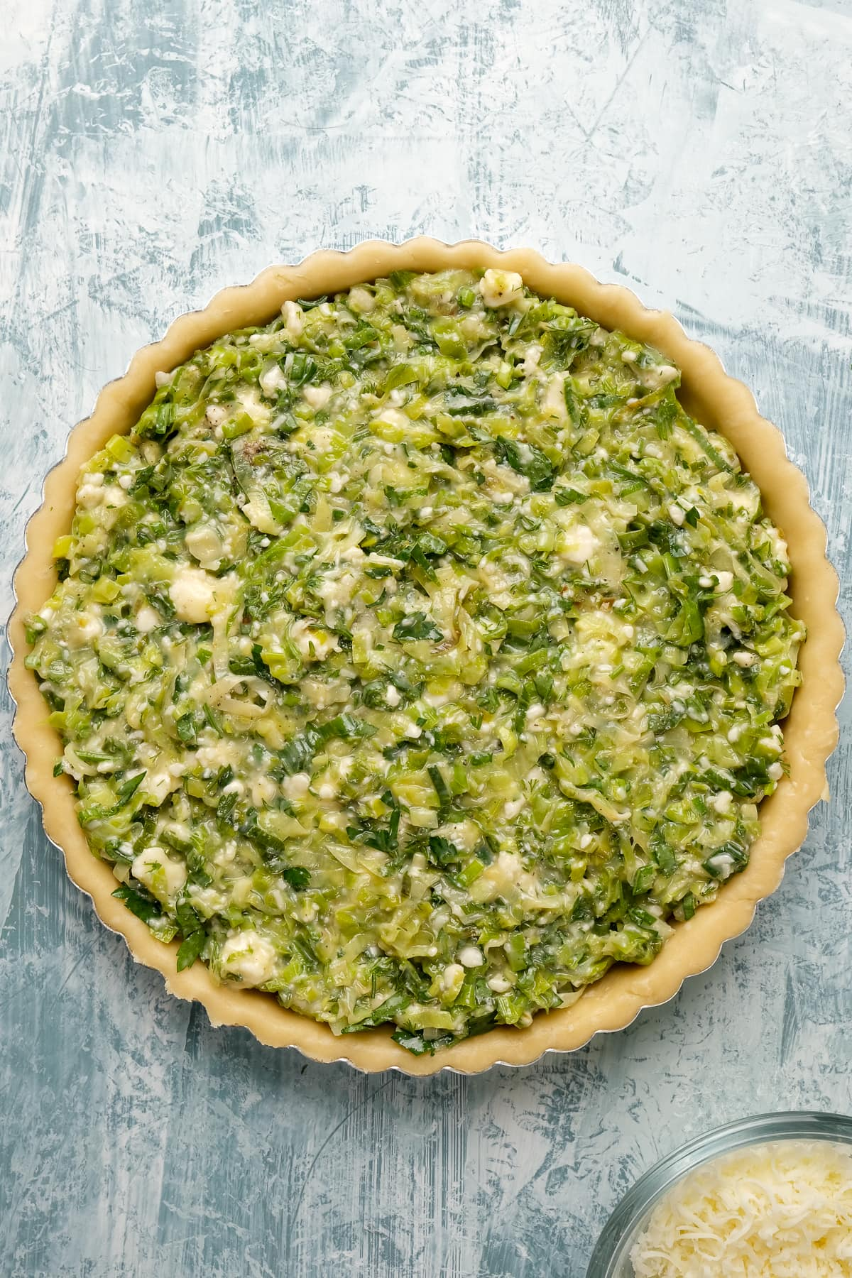 Raw quiche crust in a tart pan topped with vegetarian filling.