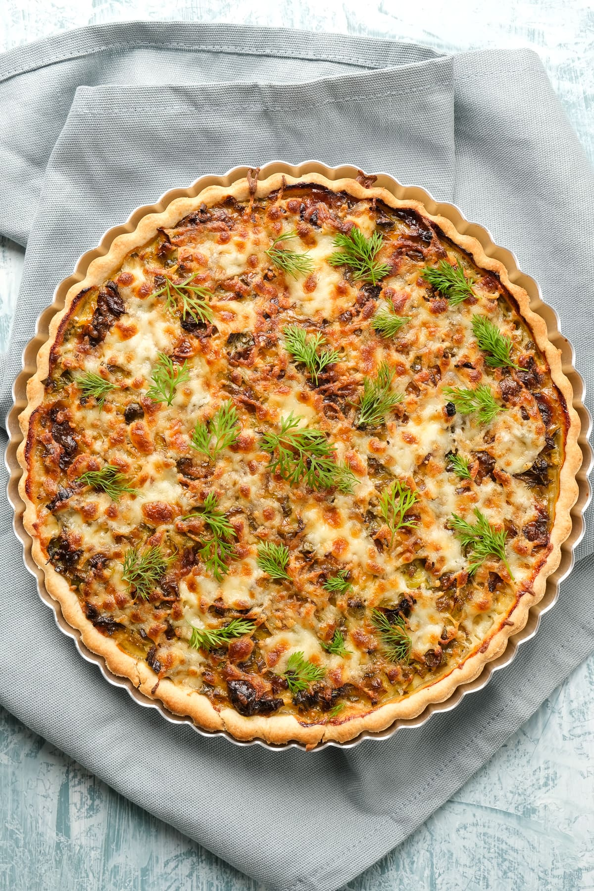 Quiche with cheese and leeks in a tart pan on a grey background.