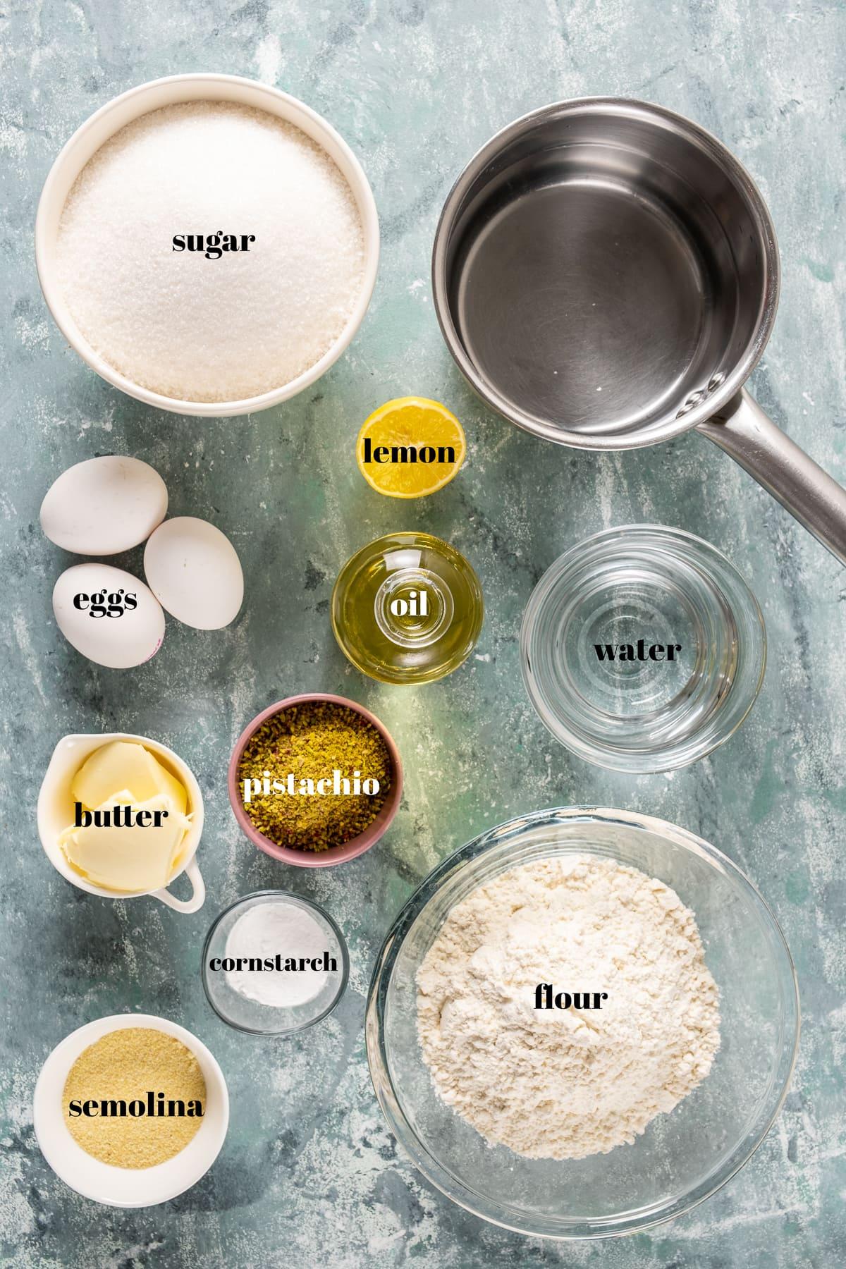 Flour, sugar, semolina, eggs, oil, pistachios, butter, lemon, cornstarch photographed on a light background.