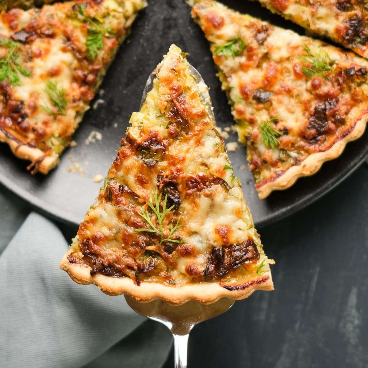 A slice of vegetarian quiche on a spatula, the rest is on a black plate on a dark background.
