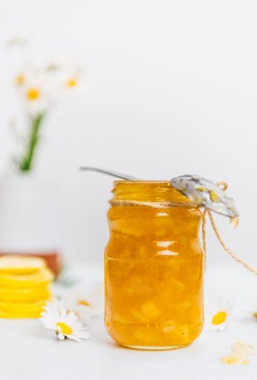 Homemade lemon jam in a jar accompanied by flowers