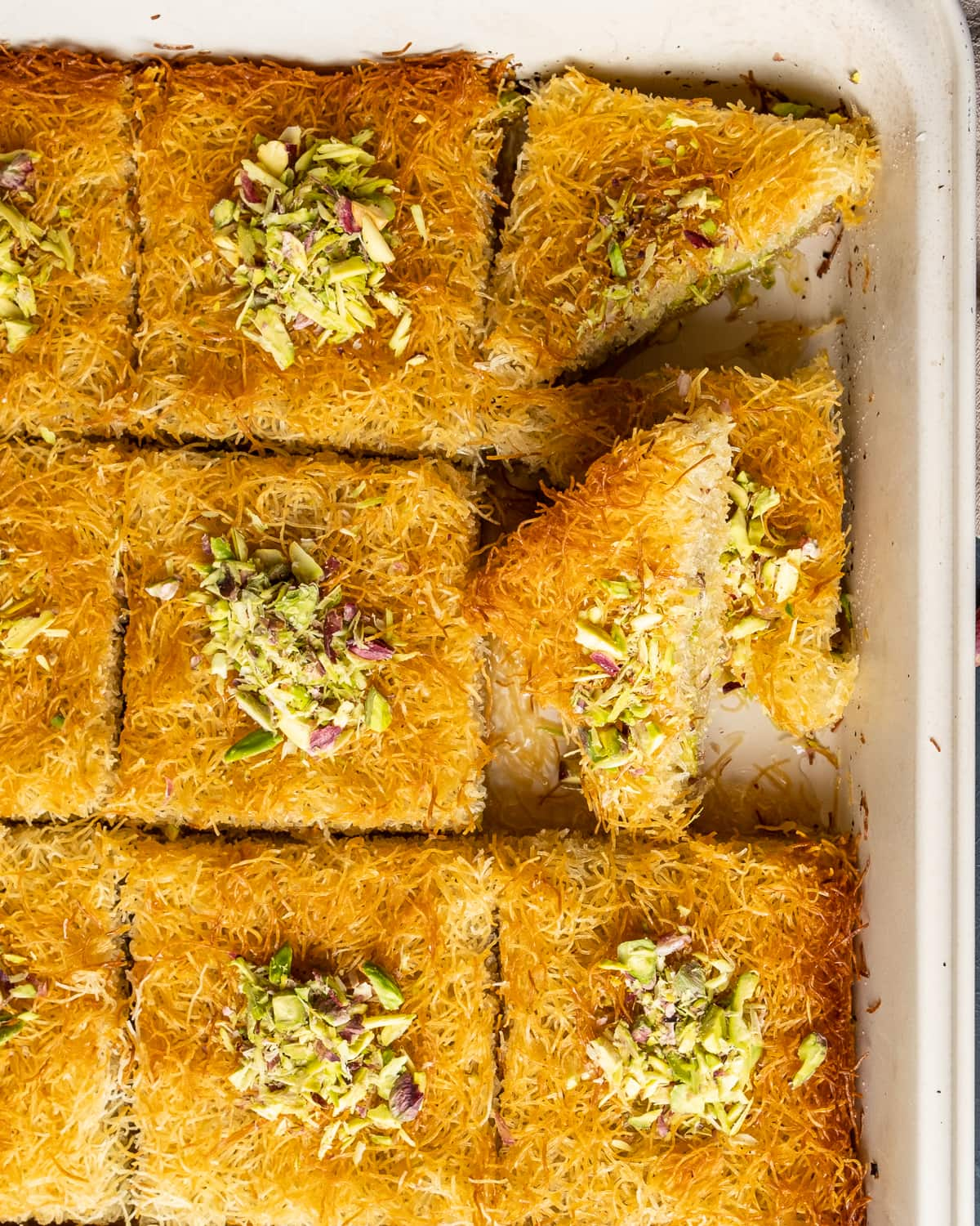 Baked golden top kadaif slices topped with crumbled pistachios in a pan.