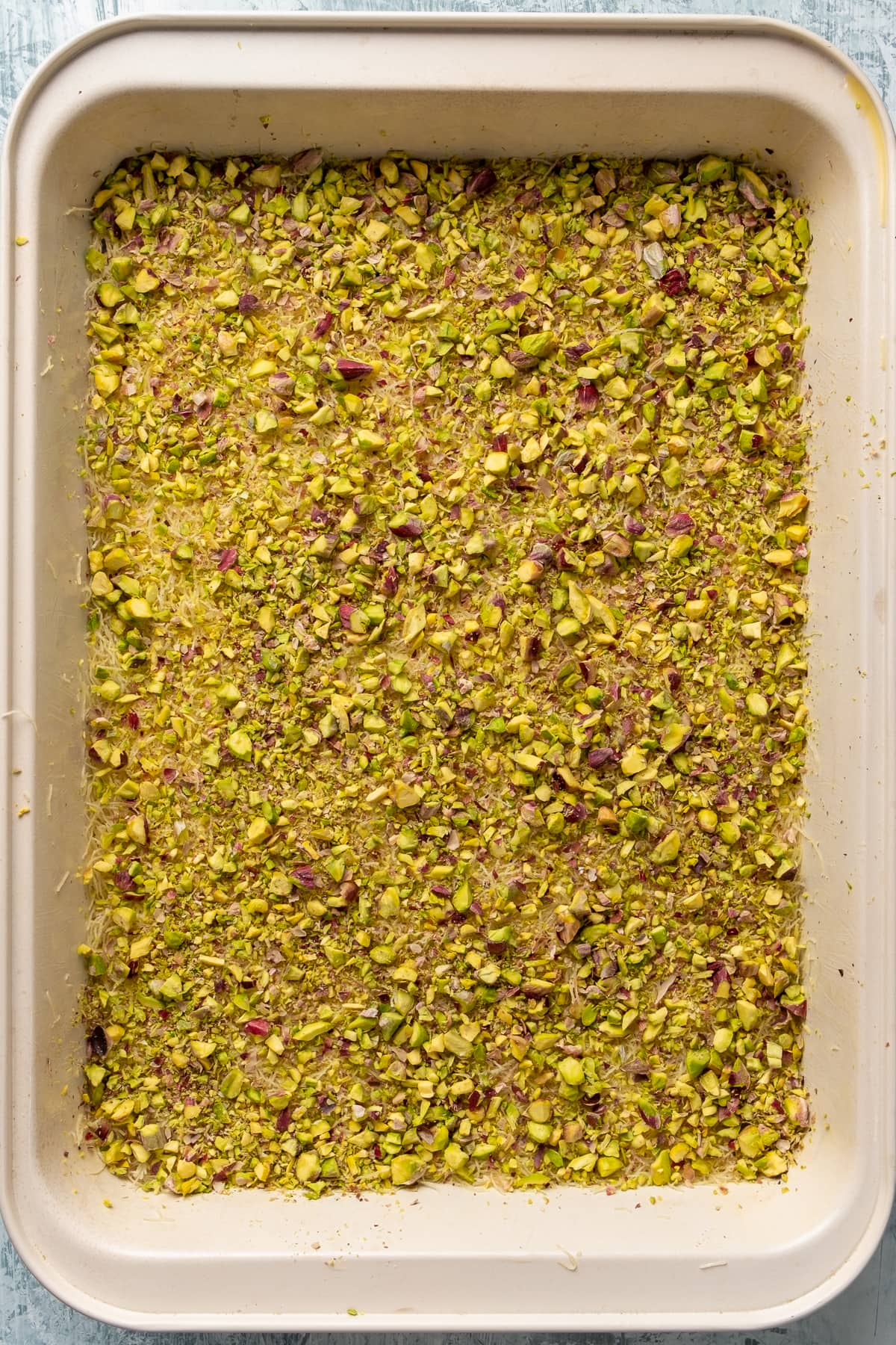 Shredded kadayif dough flattened and topped with a generous amount of crumbled pistachios.