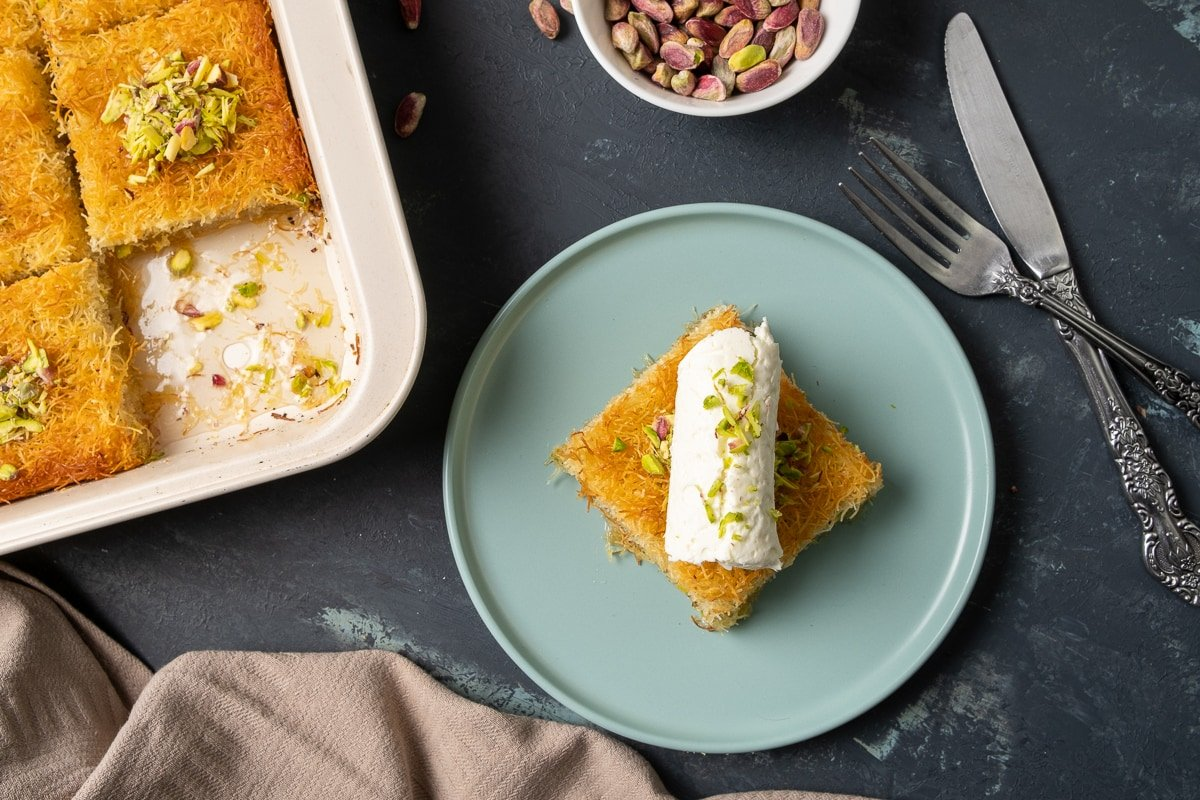 A slice of kadaif topped with a generous roll of clotted cream aka kaymak on a blueish plate, whole pistachios in a bowl and the rest of kadaif dessert in the pan on the side.