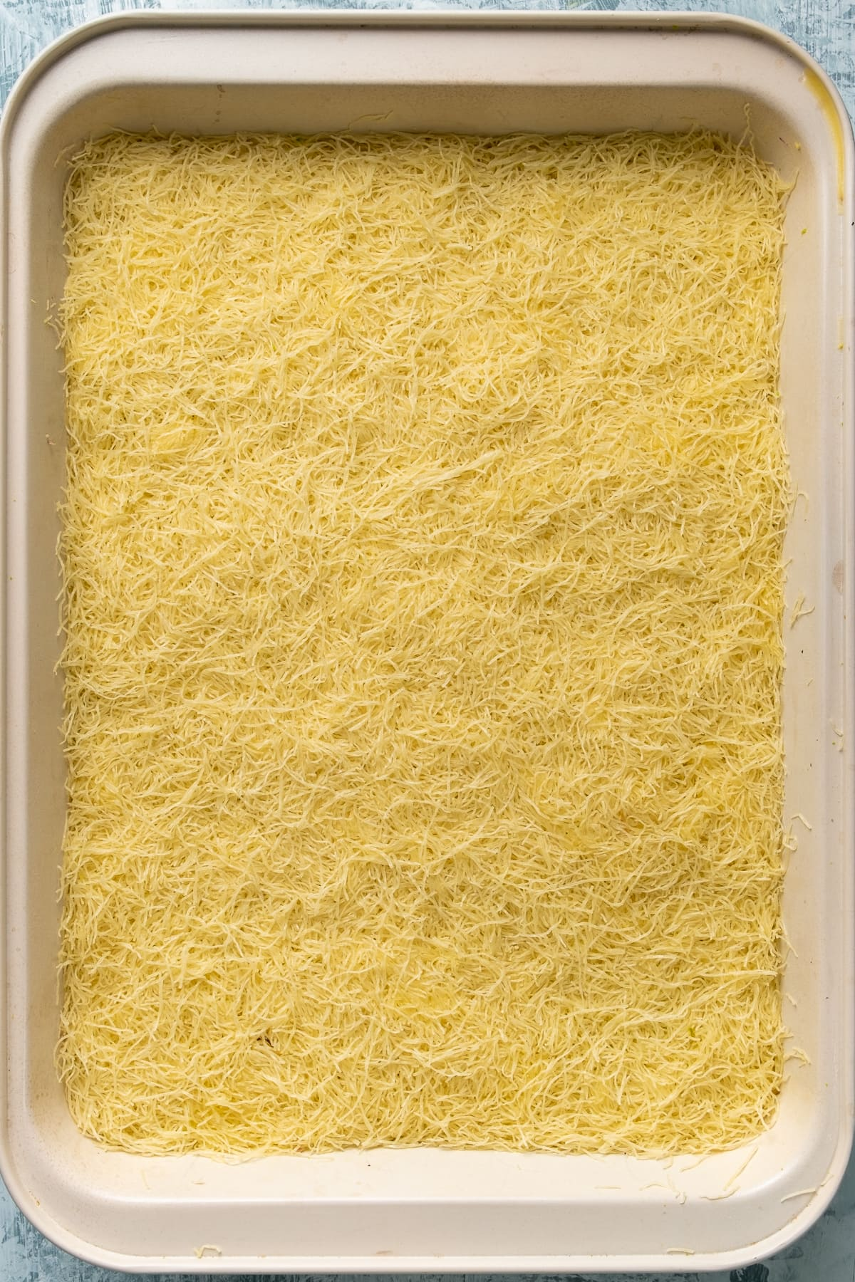 Raw kadayif ready to be baked in a rectangular pan.