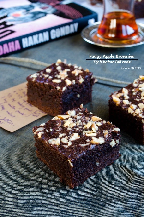 Apple and chocolate brownies photographed with a glass of tea and book behind