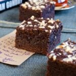 Chocolate apple brownies on a piece of paper with a recipe note