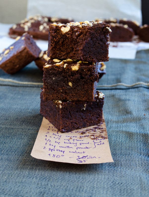 Chocolate and apple brownies stacked on a piece of paper with a recipe note