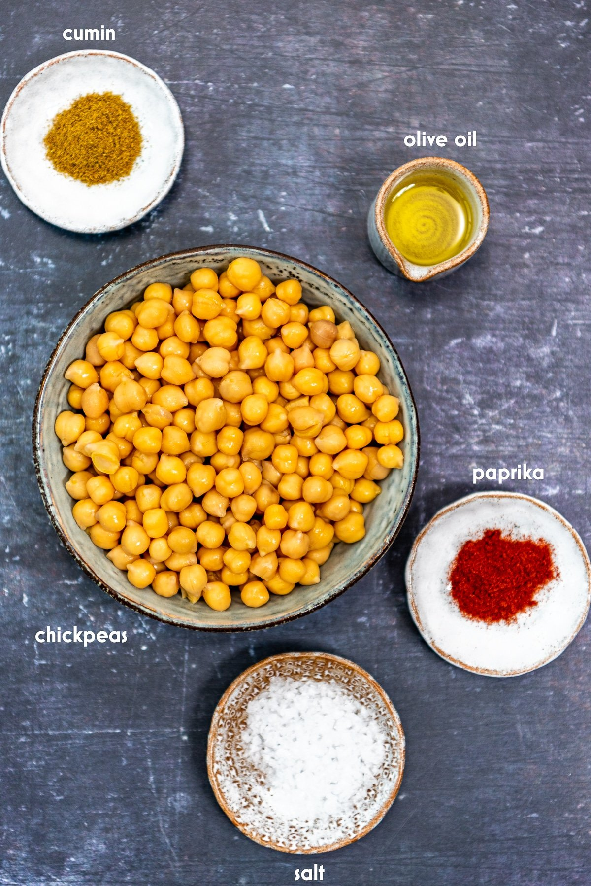 Cooked chickpeas, salt, paprika, cumin, salt and olive oil in separate bowls on a dark background.