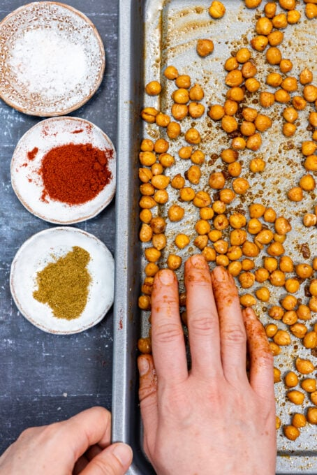 A hand coating the half roasted chickpeas with olive oil and spices on a baking sheet.