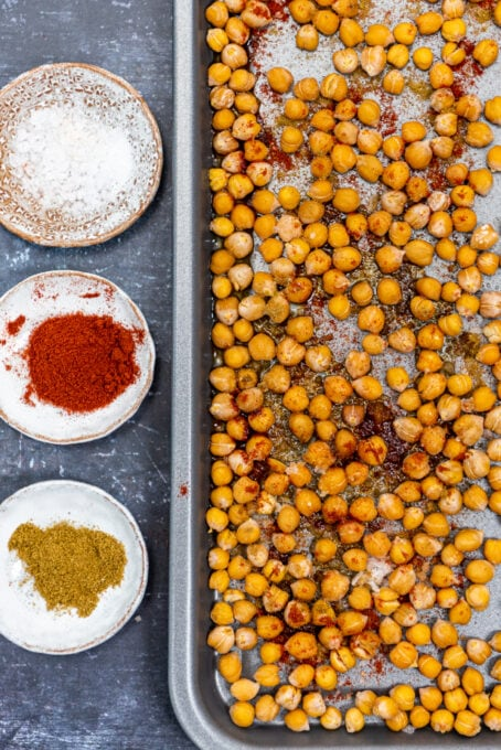 Roasted chickpeas on a baking sheet, a little spices on them. Paprika, cumin and salt in mini bowls on the side.