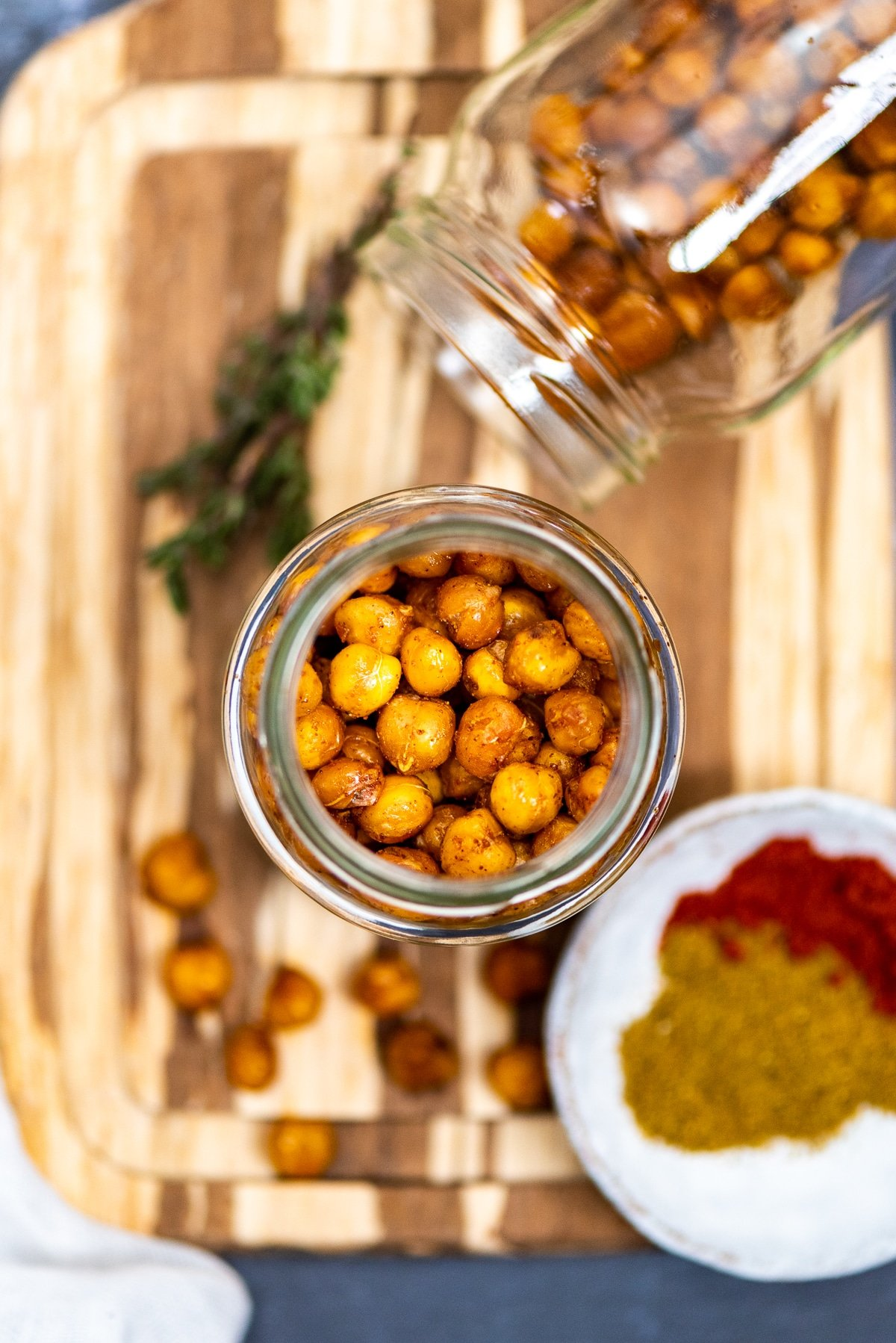 Crispy and spicy chickpeas are in two glass jars without a lid. Spices on the side.