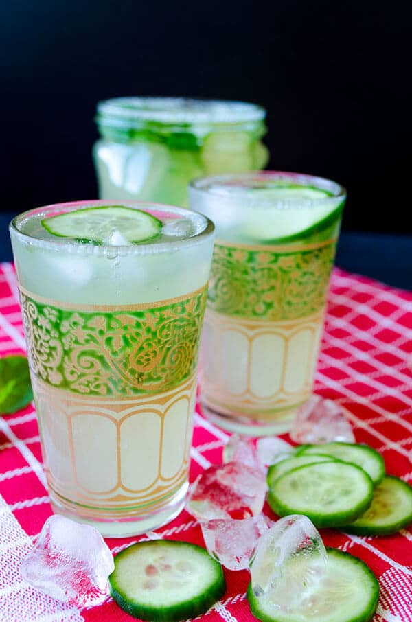 Cucumber lemonade recipe picture. Served in small glasses garnished with cucumber slices.