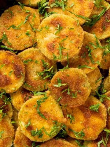 Golden fried zucchini chips garnished with parsley.