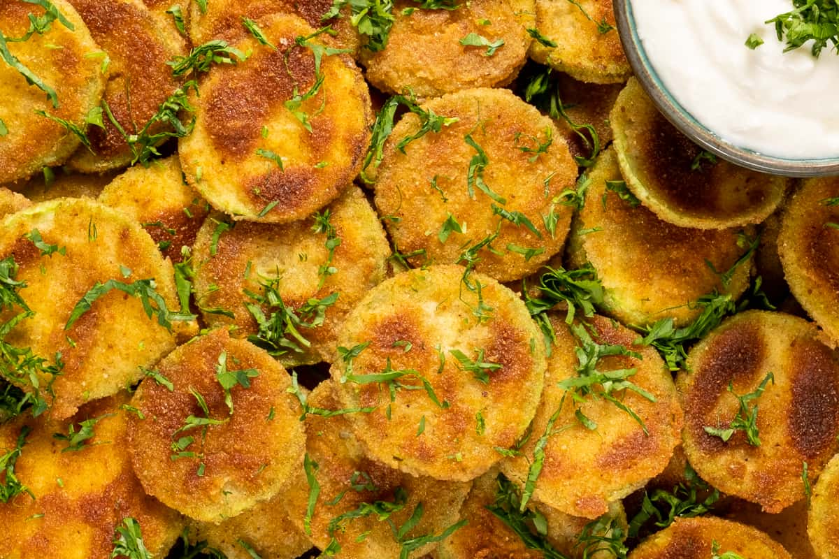Close shot of breaded zucchini chips garnished with chopped parsley.