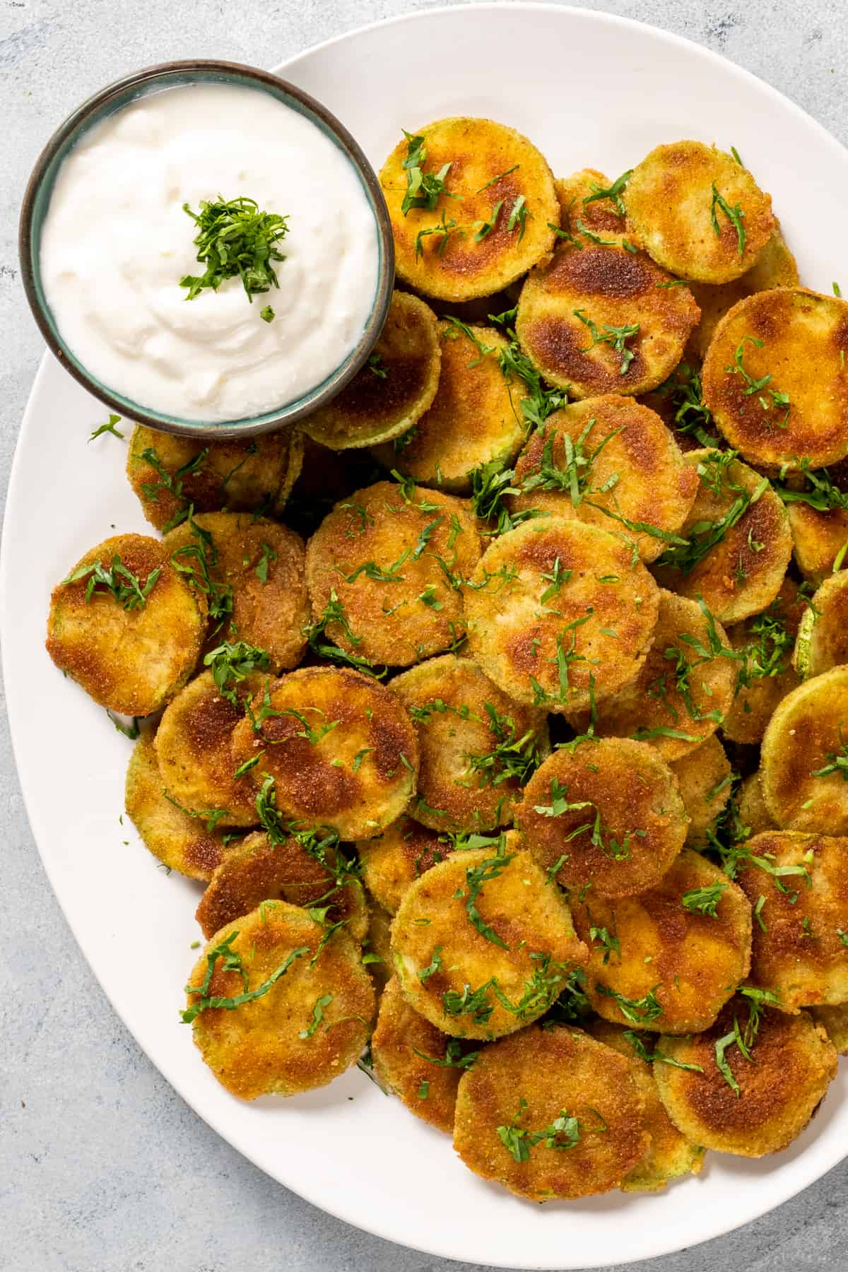 Fried zucchini chips served on a white oval dish and a small bowl of yogurt sauce on the side.