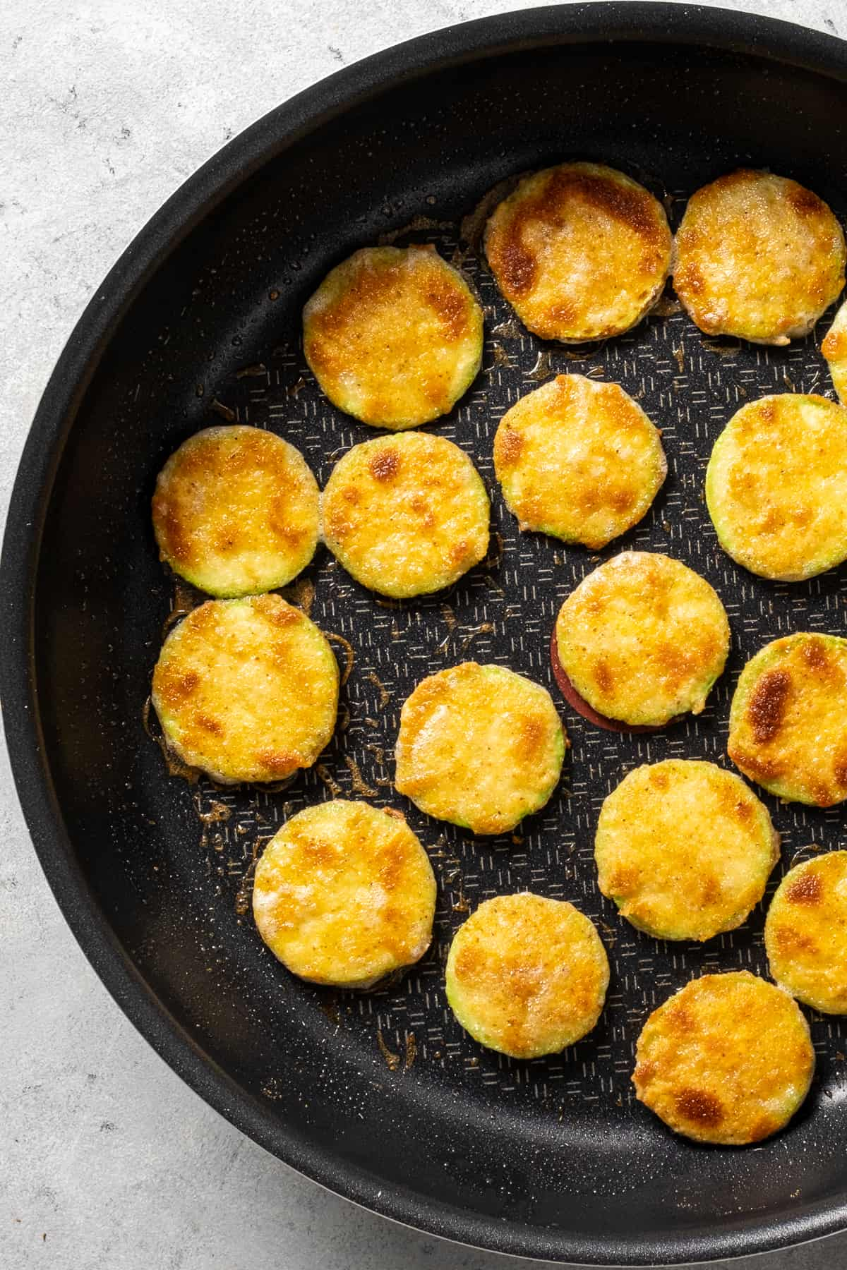 Breaded zucchini slices fried in a non-stick pan.