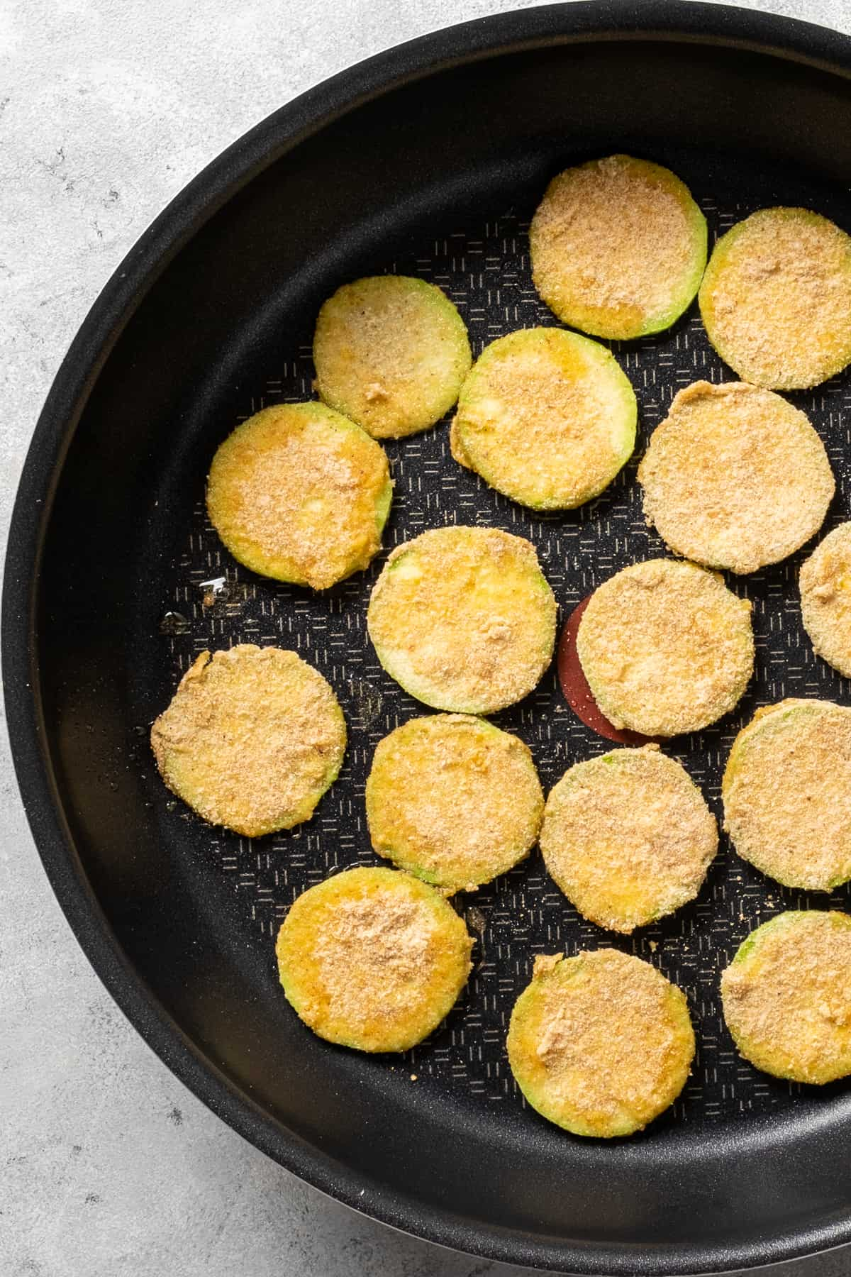 Breaded zucchini slices frying in a non-stick pan.