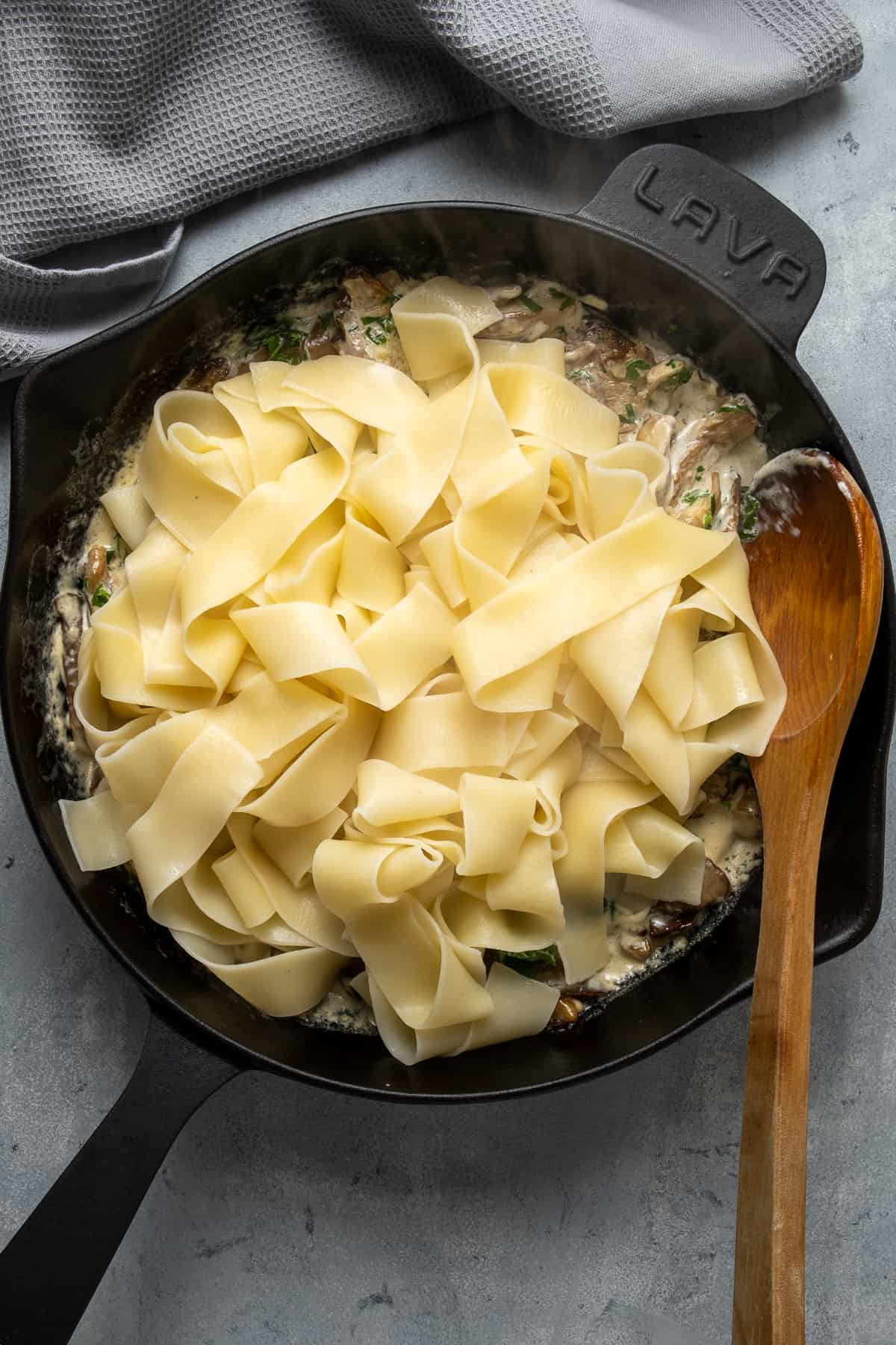 Cooked pasta combining with creamy mushroom sauce in a cast iron skillet and a wooden spoon inside it.