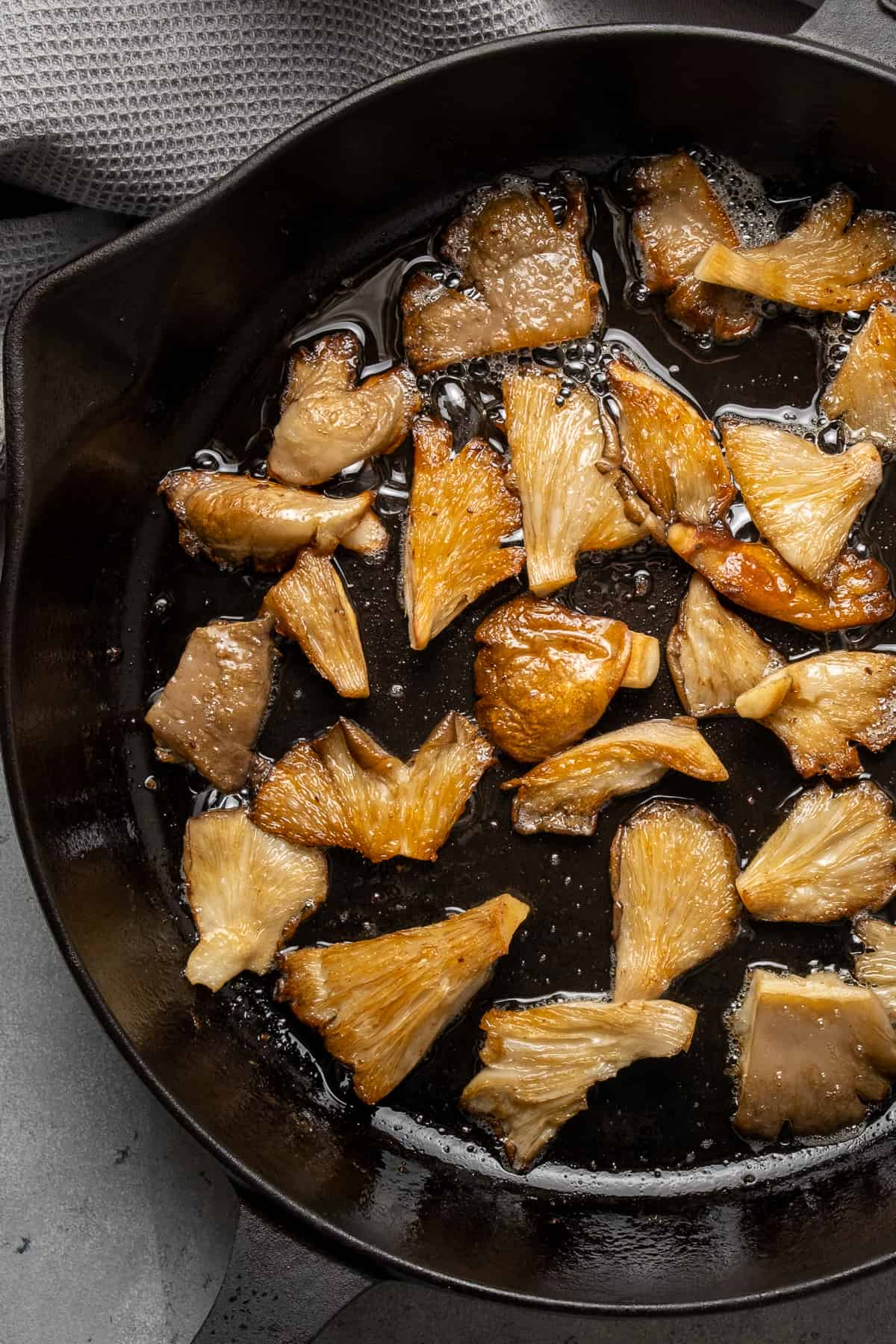 Oyster mushrooms cooking in a cast iron skillet.