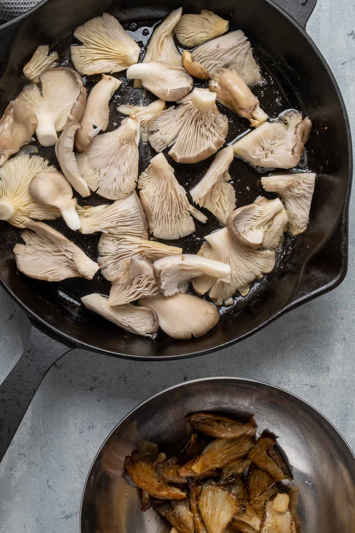 Oyster mushrooms cooking in a cast iron skillet and some fried ones are in a bowl on the side.