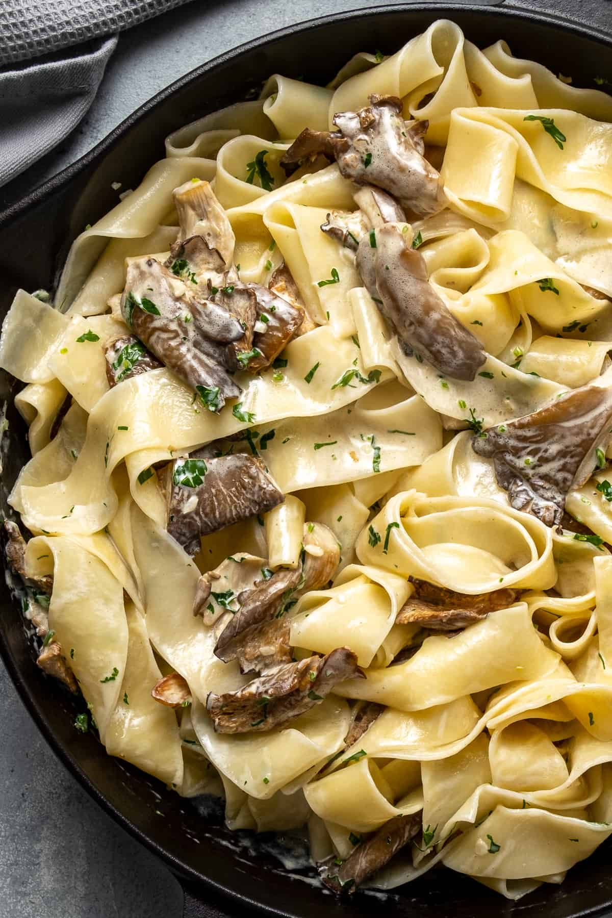 Pasta with creamy oyster mushroom sauce in a cast iron pan.