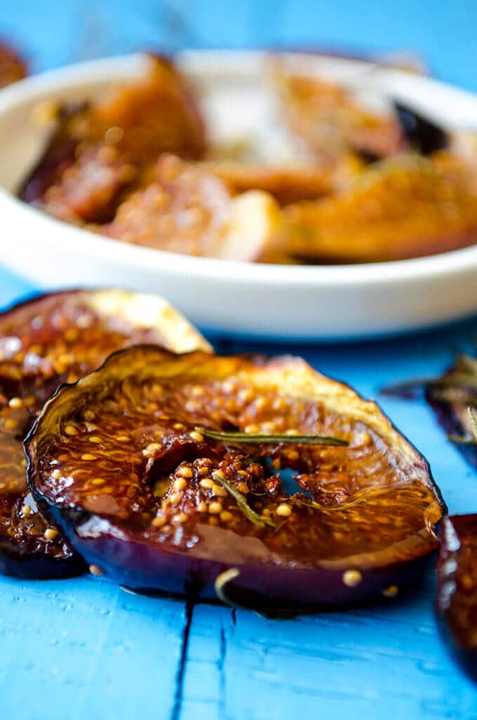 An easy fig dessert with black figs and rosemary on a blue background