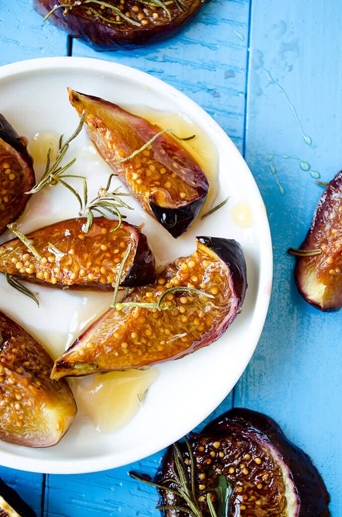 Roasted figs with honey and rosemary on a white plate