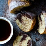 Yogurt Bundt Cake with a chocolate swirl sliced on a dark backdrop