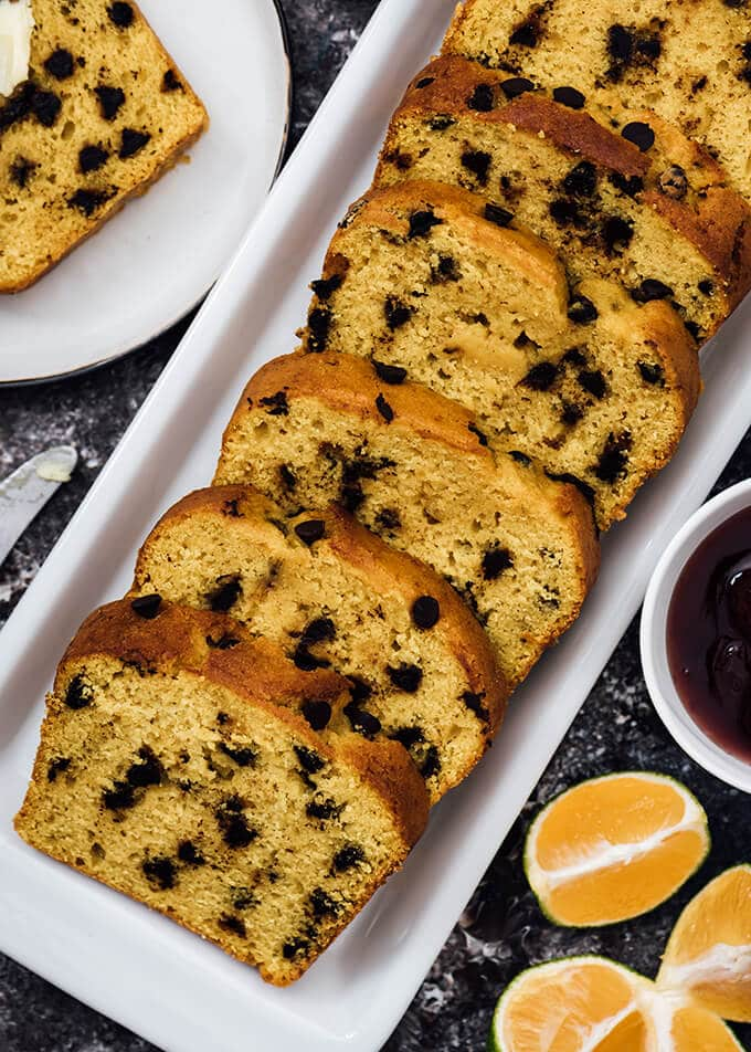 Pumpkin chocolate chip bread slices on a white plate served with jam and oranges